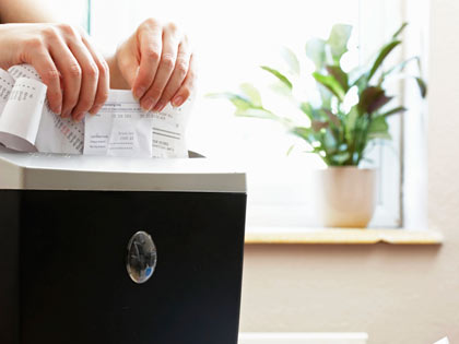 woman shredding receipts in paper shredder, close-up