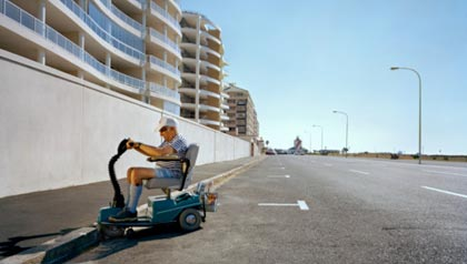 Senior man in electric scooter trying to climb curb downtown