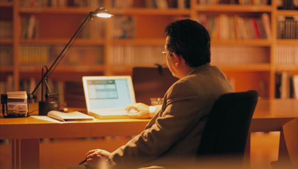 businessman using laptop in library, rear view