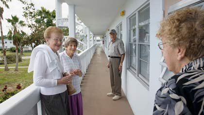 Four elderly friends on porch of apartment complex