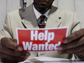 man holds up a help wanted poster