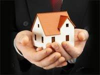 Hombre sosteniendo una casa en sus manos - Ley de ejecución de hipotecas