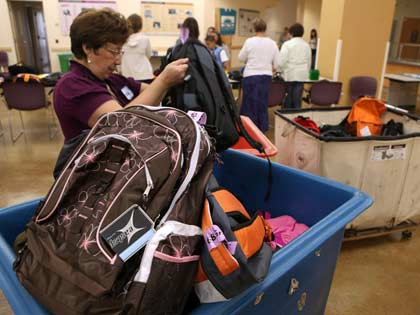 volunteer sorts through bins of backpacks