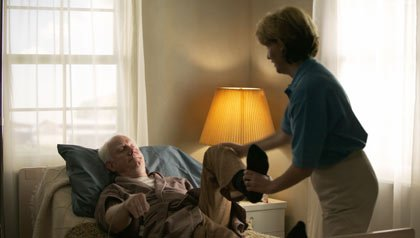 elderly man in a brown robe lays in bed and gets some physical therapy from a home nurse