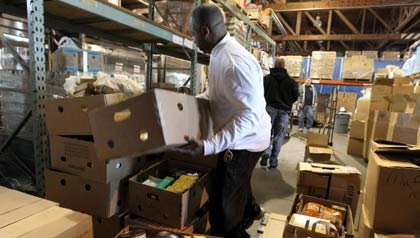 Volunteers prepare boxes with fixings for Thanksgiving meals at a food bank.
