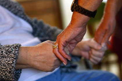 Registered nurse Susan Eager checks the strength of a patient's grip while performing a home visit