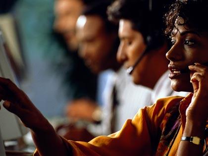 female executive sitting at computer, using telephone headset