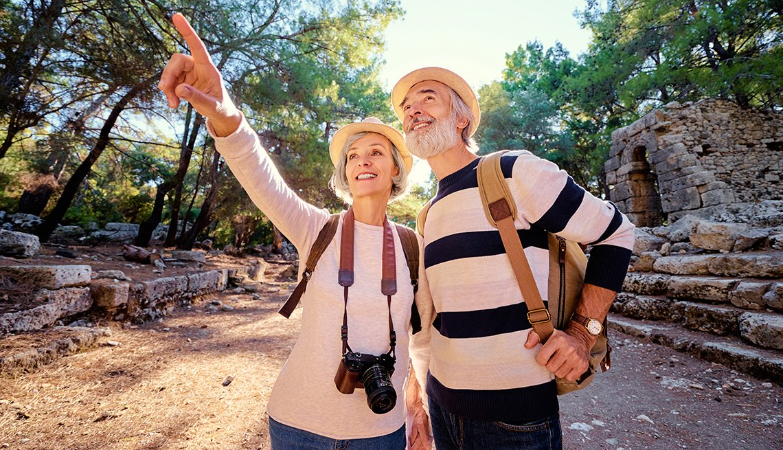 A middle-aged caucasian couple enjoy nature on a hike.