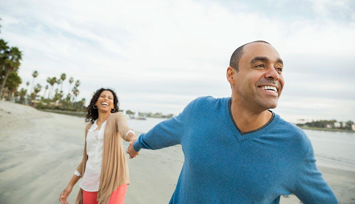 mature couple running on the beach