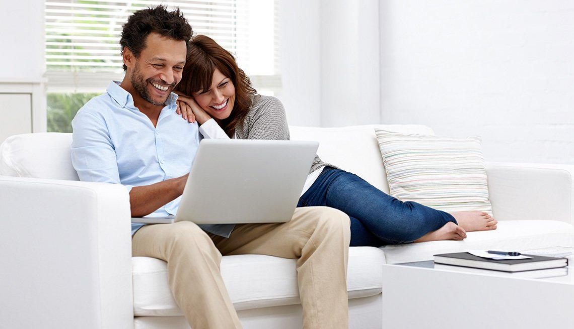 Couple with laptop on sofa