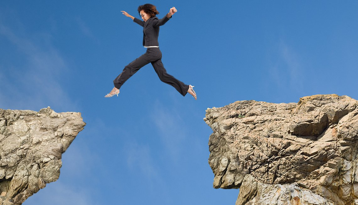 Business woman jumping a gorge