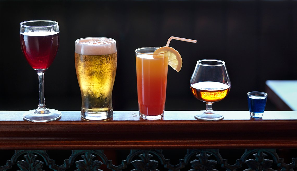 alcoholic drinks lined up on a bar