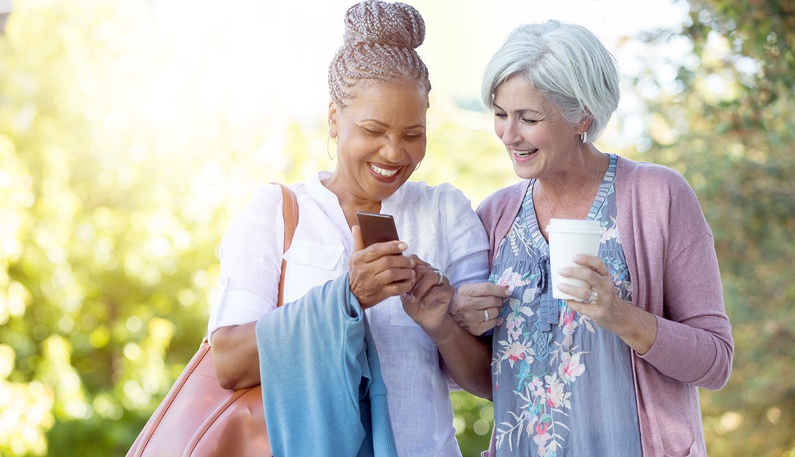 two women in park with mobile phone