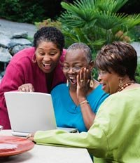 Three middle-aged African women looking at laptop