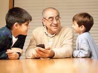Abuelo y sus dos nietos usando un teléfono inteligente - Recursos eletrónicos que le ayudarán a aprender Español