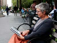woman reading an e-book in the park