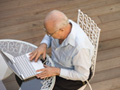 senior man working on laptop in social age