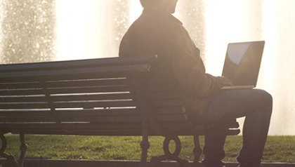 AARP Thought Leadership Topic Page- a man sits with his laptop in a public park