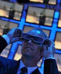 Un hombre usando unas gafas de 3D en frente de una pantalla de televisión