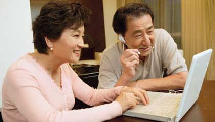 Couple sitting at table, using laptop and hands free earpiece