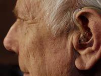 Hombre mayor usando una audífono para oir