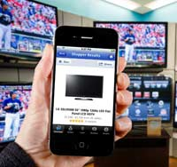 A consumer uses an app on the iPhone called Google shopper to compare prices on HD televisions by scanning the barcode of the television in front of him.
