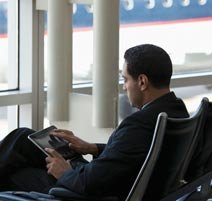 Business traveler using tablet computer in airport