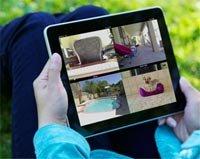 Apps que ayudan a prestar cuidado - Mujer recostada al aire libre mirando unas fotos en su iPad.