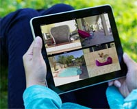 A woman outside, holding an iPad on her lap while showing house security camera images