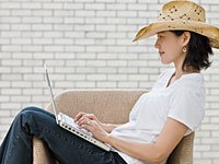 Self publishing a book is becoming easier with ebooks - a woman types on her laptop