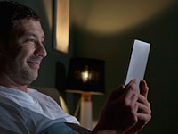 Middle-aged man uses a tablet device in bed at home