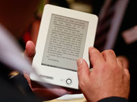 E-book readers have many advantages for older adults including different font sizes and portability-a man holds an e-reader at the Frankfurt book fair