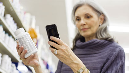 five ways to save money with smartphone mature woman shopping in store with smartphone