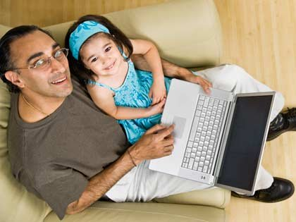 father and daughter sitting with laptop