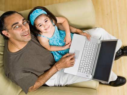 Padre e hija sentados al lado de un computador portatil