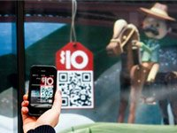 Foto de mujer de compras en la ventana de la tienda con teléfono - Cómo comprar con seguridad en los teléfonos inteligentes