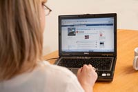 A woman using a notebook computer looks at a Facebook page.