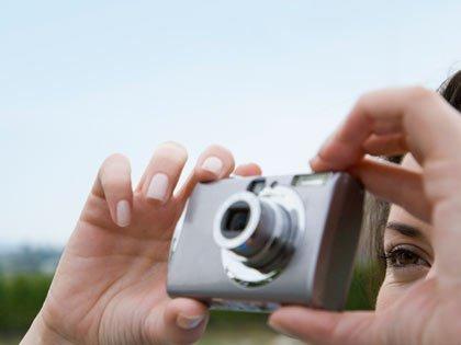 Mujer tomando una foto con un a cámara digital