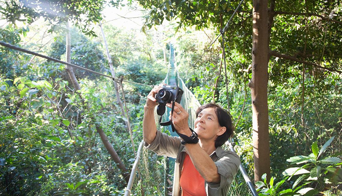 item 9 of Gallery image - Mujer mayor en un puente colgante en un bosque tropical