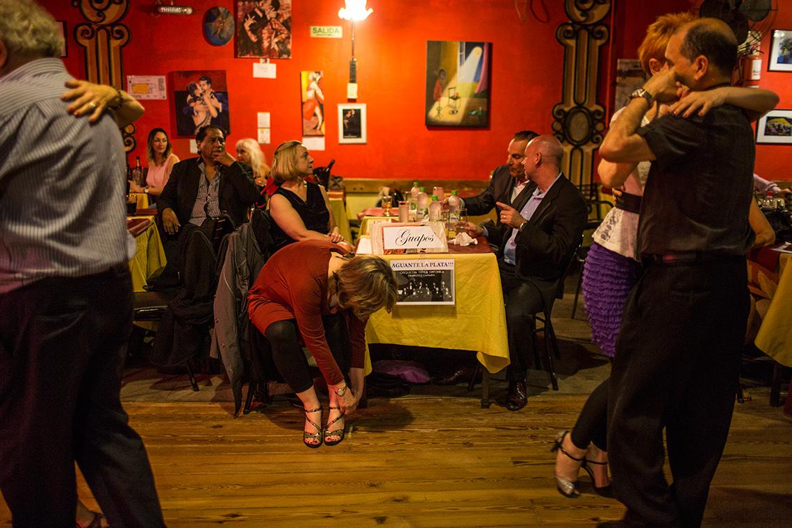 Kathleen Currie se amarra los zapatos en una mesa mientras su profesor Louis Blanco y sus compañeros de clases de tango en Little Rock, Arkansas, conversan en una mesa de una milonga en Buenos Aires.