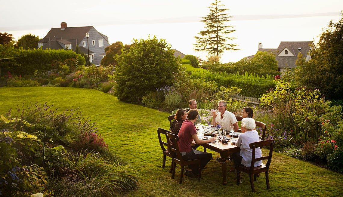 Grupo de personas comen en una mesa al aire libre