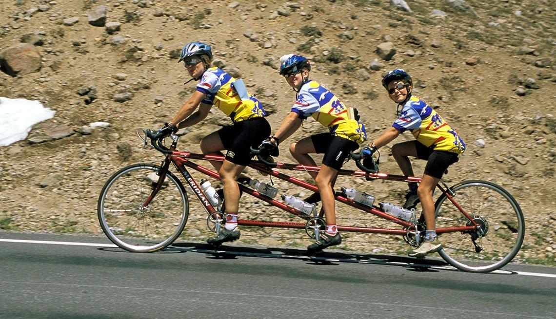 Tres personas montan una bicicleta en las montañas