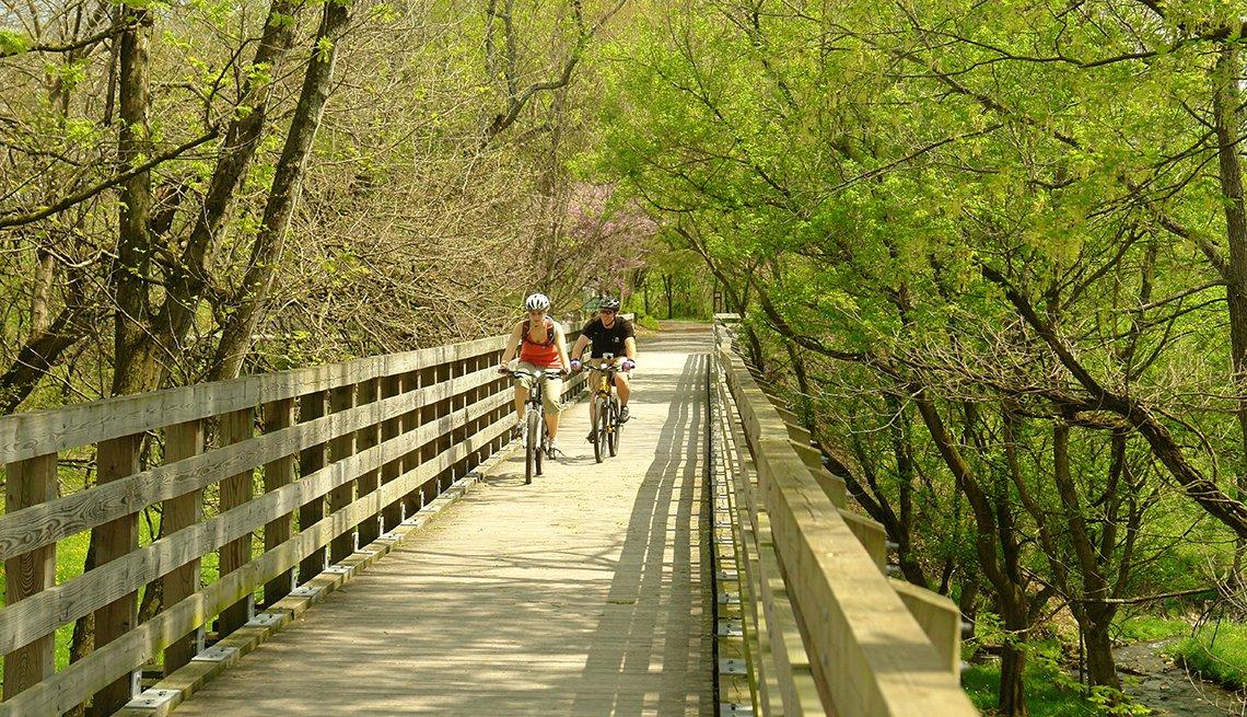 Dos personas montan bicicleta en un puente