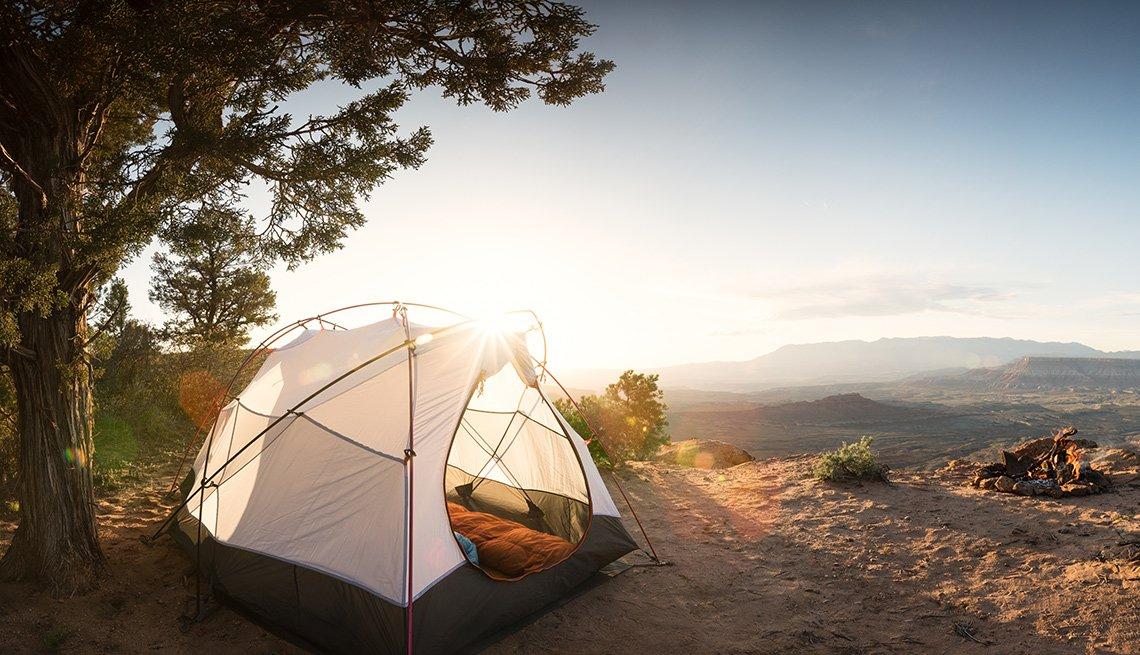 Tienda de campaña abierta durante el atardecer en una montaña
