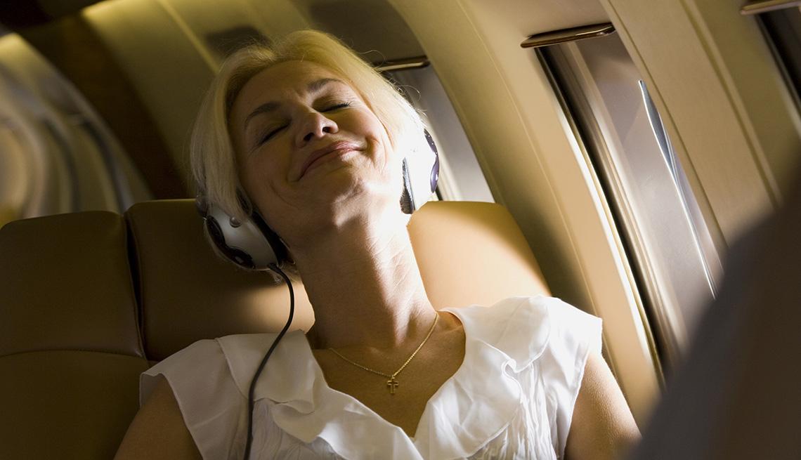 Mujer mayor usando unos audífonos en la silla de la ventana de un avión y las cosas que deberías saber antes de tomar un vuelo.