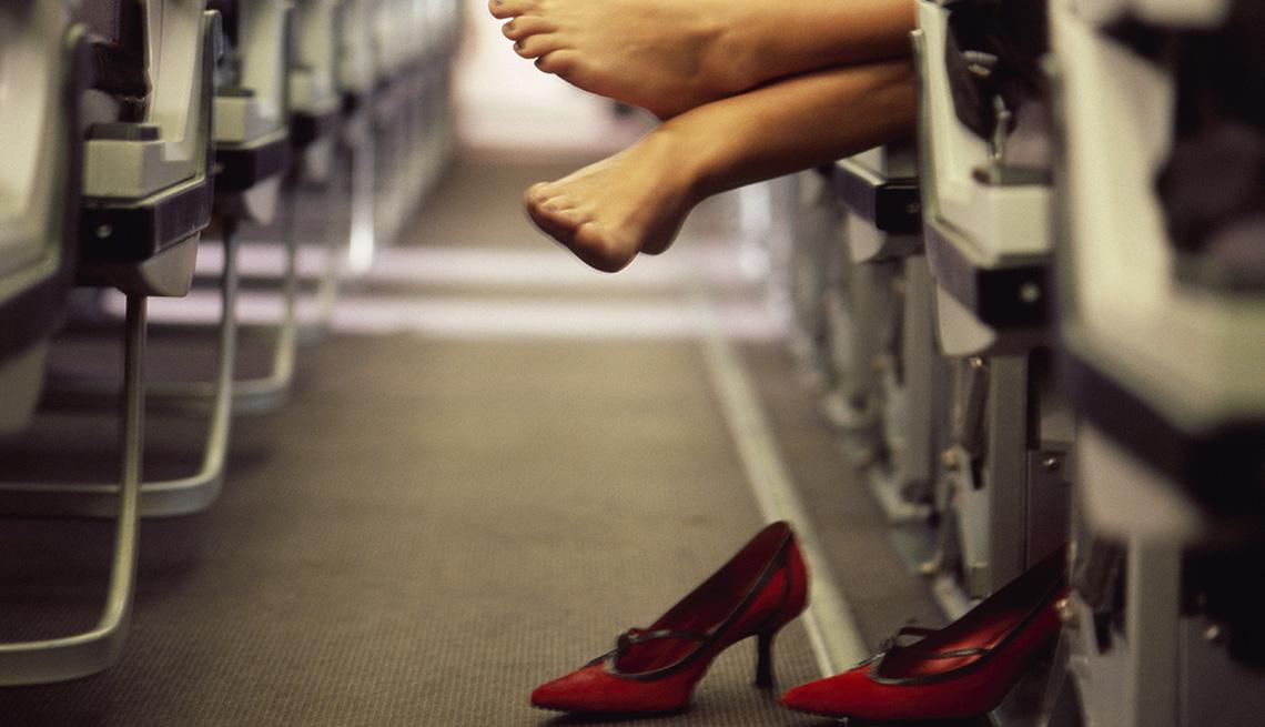 Pies de mujer acostada en un avión