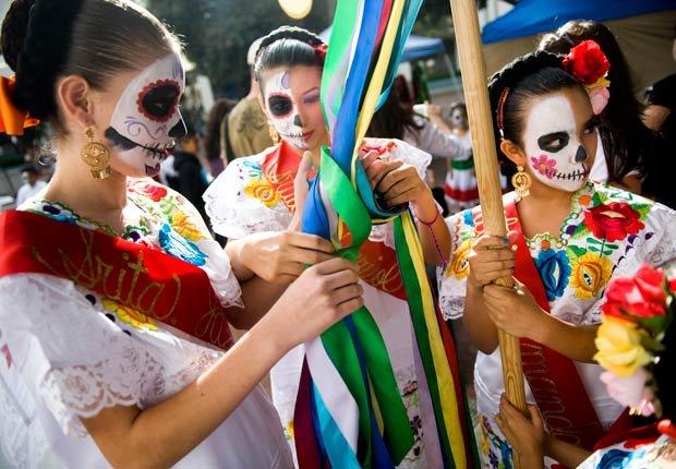 Tres chicas esperan el inicio de su rutina en la Noche del Día de los altares de muertos en el centro de Santa Ana - Día de los Muertos