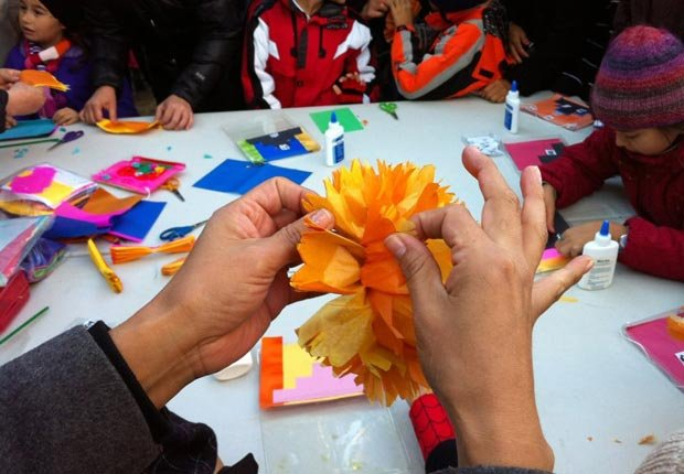 Children's hands make marigolds out of paper at a Day of the Dead workshop - Day of the Dead