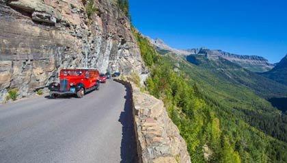 Bus rojo en el ir al camino del Sol en el Parque Nacional Los Glaciares en las Montañas Rocosas de Montana - 9 Grandes rutas para este verano