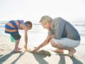 Grandfather and grandson digging in sand at beach in San Diego, Calif., Multigenerational vacations  (Hero Images/Getty Images)